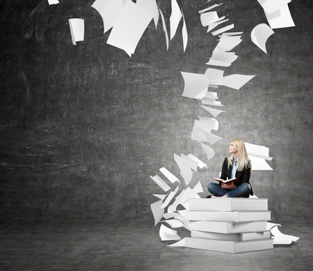 pile up: young woman sitting on a pile of books with an open book on her knees thinking about future or looking for a solution of a problem, black wall at the background with sheets of paper flying around, a concept of finding a solution