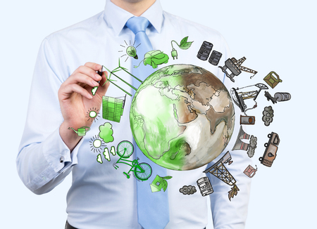 ecology  environment: man pointing at the brown picture of oil industry components and green eco energy arranged in circle, earth in the centre, concept of environment