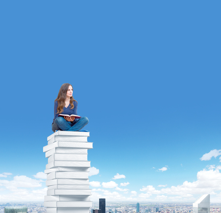 heights job: young woman sitting on a pile of books with an open book on her knees thinking about future, blue sky and a city viewl at the background, concept of dreaming