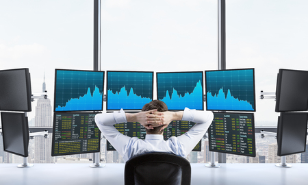 depository: Rear view of a relaxing trader who is sitting in front of a trading station which consists of four screens with financial data. A concept of forex trading. New York panoramic view