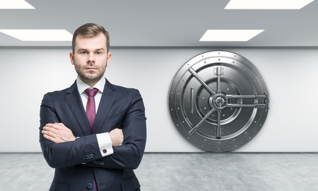 businessman with arms crossed standing in front of a big locked round metal safe in a bank depository,  a concept of security,  front view, Foto de archivo