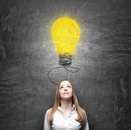 young woman standing in front of a black wall looking at a yellow light bulb, looking for a solution of a problem, black wall at the background, a concept of finding a solution Stock Photo