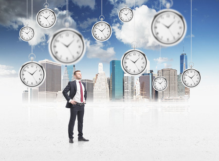 streamlining: Man standing with his head up, isolated, several models of pocket watches hovering in the air. A concept of a value of time in business. Singapore at the  background. Stock Photo