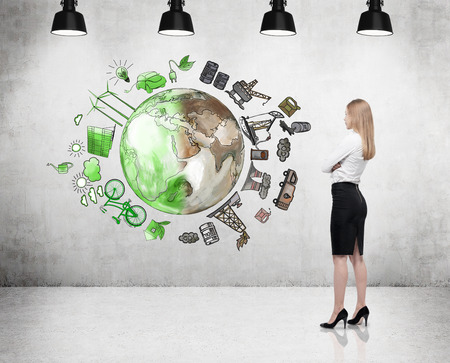 disaster supplies: woman in front of the wall thinking about oil production and pollution, brown illustration of oil industry components and green eco energy on concrete wall arranged in circle, concept of environment