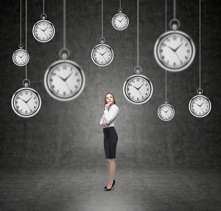 streamlining: Woman standing and thinking, isolated, several models of pocket watches hovering in the air. A concept of a value of time in business. Black background.