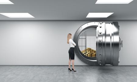 piramide humana: joven de pie en frente de un gran redondo de metal desbloqueado segura en un dep�sito bancario con una pir�mide de barras de oro y los cierres cajas en el interior, un concepto de seguridad y servicio al cliente