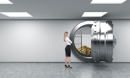 human pyramid: young woman standing in front of a big unlocked round metal safe in a bank depository with a pyramid of gold bars and lock-boxes inside,  a concept of security and client service