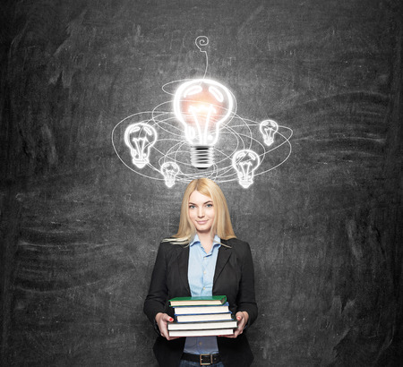 young woman holding books, standing in front of a black wall looking in front, looking for a solution of a problem, drawn bulbs over her head, a concept of finding a solution