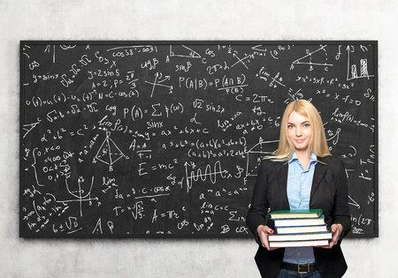 alumni: a young blonde girl standing and holding books, blackboard with small signs and dawings at the background, a concept of studying and knowledge aquisition Stock Photo