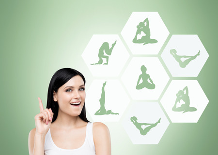 Beautiful young woman smiling with finger up thinking about taking up sport exercise, yoga, illustrations of several exercises in hexagons near her, green background, concept of healthy life