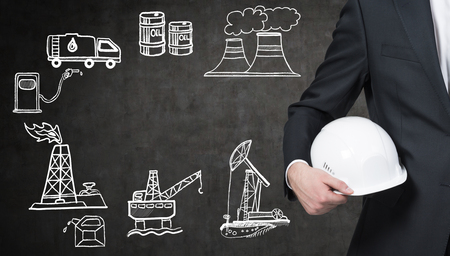 a man standing to the left in front of the black wall, half view, holding a white helmet, illustration of oil industry components on the wall arranged in a circle, concept of environmental pollution