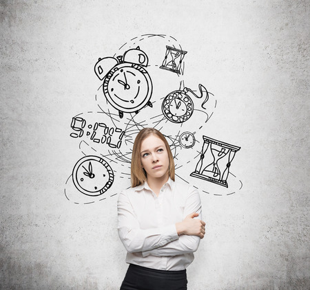 two minds: young pretty businesswoman thinking about time, in two minds, several models of clocks drawn behind. A concept of a value of time in business. Concrete wall at the background Stock Photo