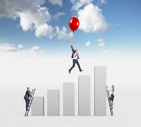 carrer: businessman in a suit flying happily holding a balloon over carrer ladder, man and woman climbing ladders, blue sky at the background, concept of success and career growth Stock Photo