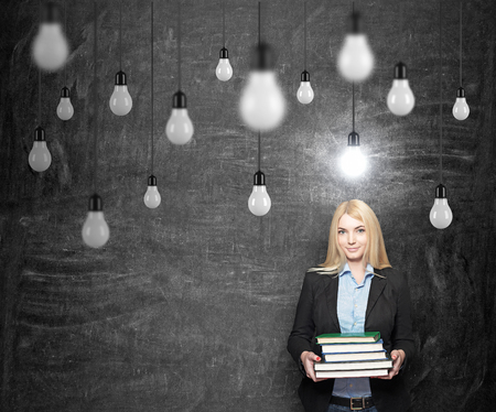 alumni: young woman holding books, standing in front of a black wall looking in front, looking for a solution of a problem,  bulbs hovering from above, a concept of finding a solution