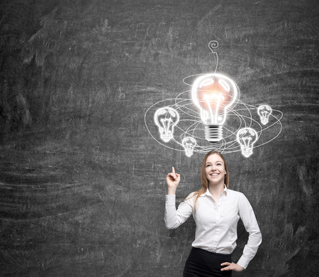alumni: young woman standing in front of a black wall pointing at a white light bulb, looking for a solution of a problem, drawn bulbs over her head, a concept of finding a solution
