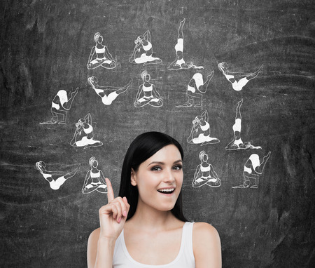 young woman smiling: Beautiful young woman smiling with finger up thinking about taking up sport exercise, yoga, illustrations of several exercises around her, black background, concept of healthy life Stock Photo