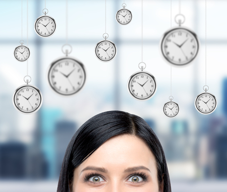streamlining: Woman thinking about time, half face seen, several models of pocket watches hovering in the air. A concept of a value of time in business. blurred office window at the background.