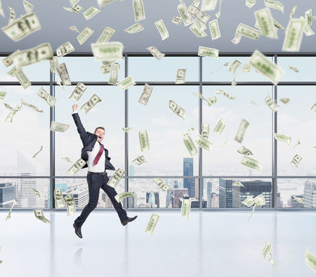 buy shares: businessman in a suit jumping happily with his hand up, office open space, money falling from above, new york panoramic view at the background, concept of success