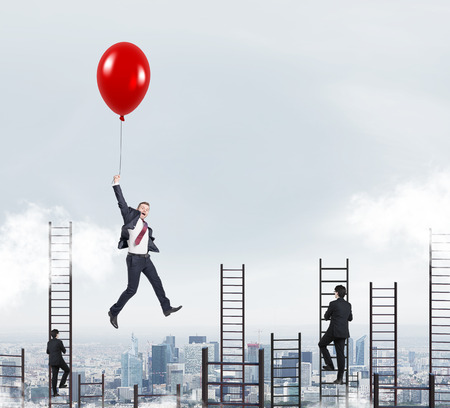 businessman in a suit flying happily holding a balloon over Paris, men climbing ladders, concept of success and career growth Stock Photo