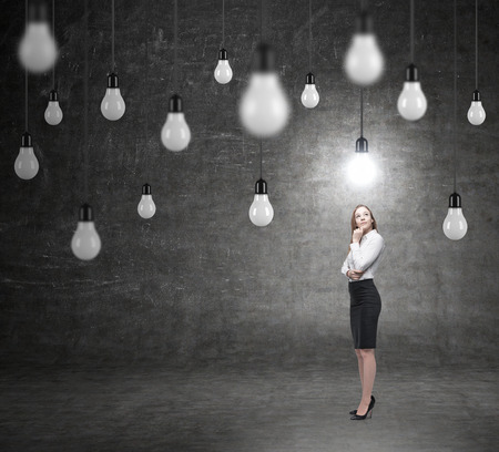 alumni: young woman standing in front of a black wall looking up with hand to the chint, looking for a solution of a problem, bulbs hovering from above, a concept of finding a solution