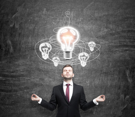 alumni: young man standing in front of a black wall in posture of meditation with eyes closed, white light bulb above, looking for a solution of a problem, drawn bulbs over his head, a concept of concentration Stock Photo