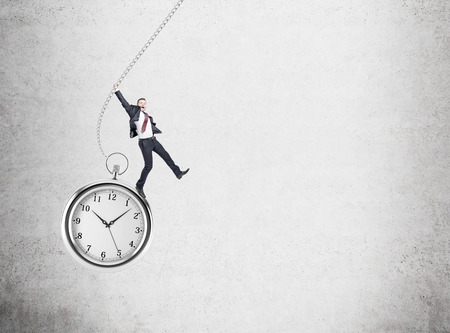 streamlining: small happy young businessman swinging on huge pocket watch. Concrete wall at the background. Concept of playing with time