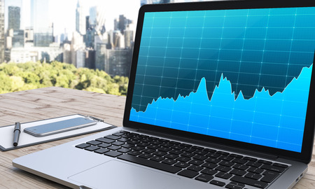 note pad and pen: laptop with blue graphs, note pad, pen and smartphone to the left, on a wooden table, panoramic view of New York at the background, concept of business, 3D rendering, side view