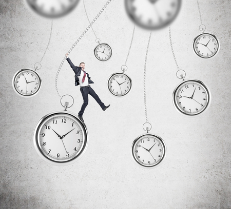 streamlining: happy young businessman swinging on pocket watch, other pocket watches hovering around. Concrete wall at the background. Concept of playing with time