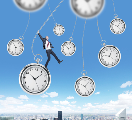 streamlining: happy young businessman swinging on pocket watch, other pocket watches hovering around, in the sky. New York at the background. Concept of playing with time Stock Photo