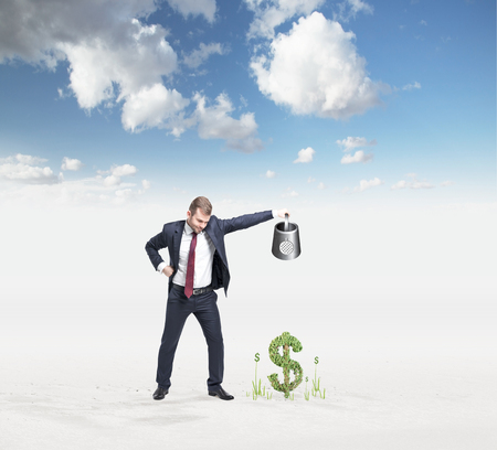 affluence: businessman holding watering can pouring water on money so that it grows, blue sky at the background, concept of money accumulation
