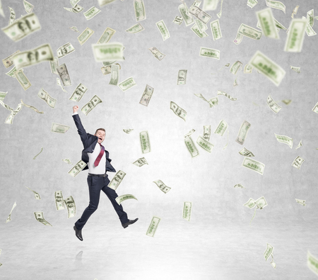forex: businessman in a suit jumping happily with his hand up, money falling from above, concept of success