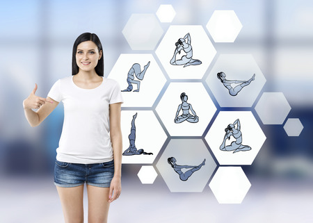 recommending: Beautiful young woman pointing to illustrations of several yoga exercises in hexagons recommending sport, blurred background, concept of healthy life