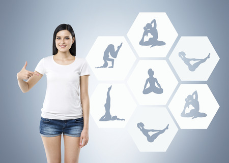 recommending: Beautiful young woman pointing to illustrations of several yoga exercises hexagons recommending sport, grey background, concept of healthy life