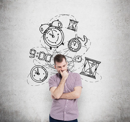two minds: young man with his ��� to the chin thinking about time, in two minds, several models of clocks drawn behind. A concept of a value of time in business. Concrete wall at the background