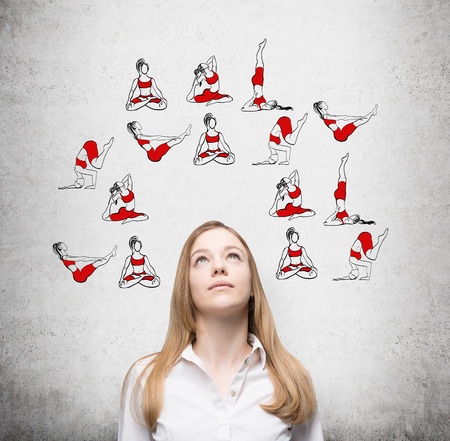 Beautiful young woman looking up thinking about taking up sport exercise, yoga, red illustrations of several exercises in around her, concrete background, concept of healthy life Stock Photo