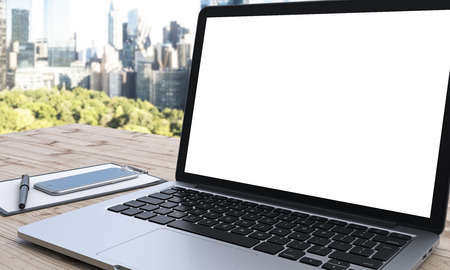 note pad and pen: blank laptop monitor  note pad, pen and smartphone to the left on a wooden table, panoramic view of New York at the background, concept of business, 3D rendering, side view Stock Photo