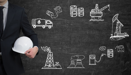 disaster supplies: a man standing to the right in front of the black wall, half view, holding a white helmet, illustration of oil industry components on the wall arranged in a circle, concept of environmental pollution