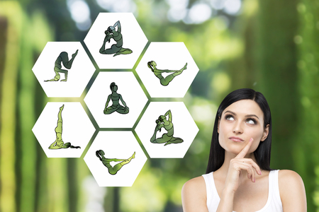 Beautiful young woman with eyes raised up hand to the chin dreaming about taking up sport exercise, yoga, illustrations of several exercises near her, green background, concept of healthy life Stock Photo