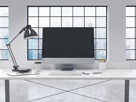note pad and pen: Workplace in the office, computer, keyboard, mouse, smartphone, lamp, note pad, pen, pencil glass, coffee on the table, window behind the table, blurred city view, front view. Concept of work Stock Photo
