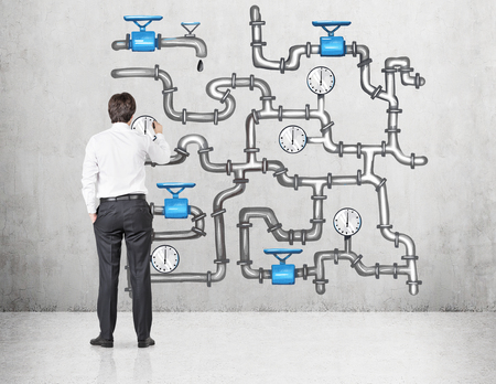 turns: Man standing in front of an illustration of sophisticated pipeline on the concrete background, drawing. Back view. Concept of oil transportation