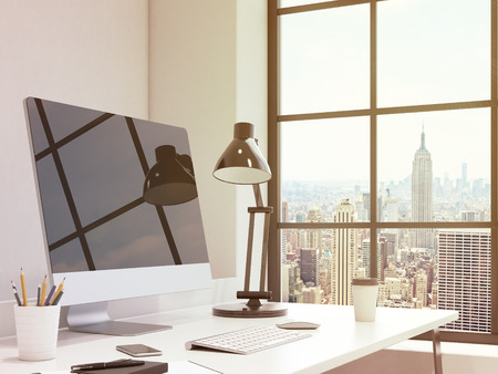 note pad and pen: workplace in the corner, computer, keyboard, mouse, smartphone, lamp, note pad, pen, pencil glass, coffee on the table, chair in front, window with New York view to the right. Concept of work Stock Photo