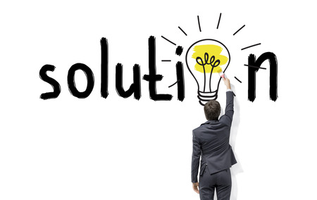 finding: Young businessman painting a bright yellow bulb with a brush in the word solution instead of the second o on the white wall. Back view. Concept of finding a solution.