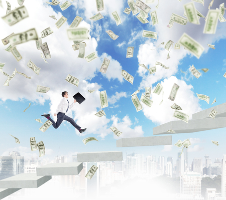 Successful young businessman with a folder in hand running upstairs, Paris and blue sky at the backgroundl, dollar banknotes falling from above. Concept of career growth Stock Photo
