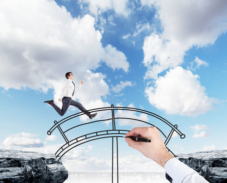 wallstreet: A young businessman crossing the drawn bridge between two cliffs, hand drawing the bridge, blue sky at the background. A concept of bridging the gap. Stock Photo