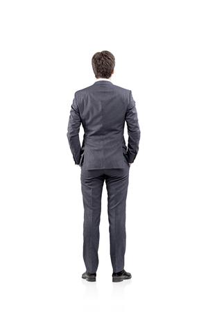 espalda: Joven empresario de pie con las manos en los bolsillos. Vista trasera. Concepto de pensamiento