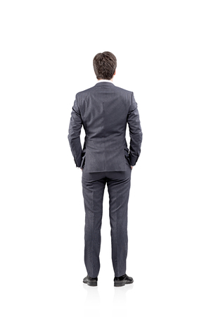 back view: Young businessman standing with his hands in pockets. Back view. Concept of thinking Stock Photo
