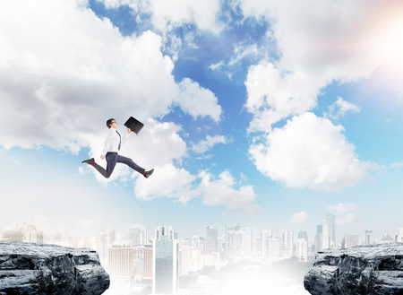 A young businessman with a folder in his hand jumping between two cliffs, New York and  blue sky at the background. A concept of bridging the gap.