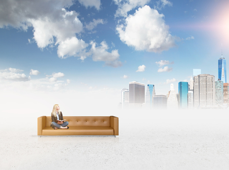 A young woman sitting and looking up on a brown leather sofa standing in the middle of nowhere. Blue sky and sun and Neww York at the background. Concept of dreaming.