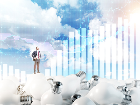 smart goals: Young man with hands in pockets standing on huge scattered bulbs, proud of himself. Blue sky and graphs at the background. Concept of new ideas.