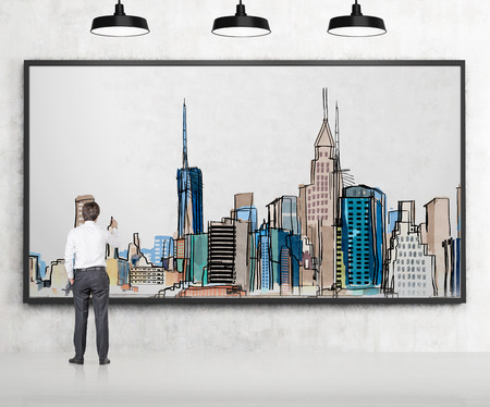 earing: Young businessman drawing a picture of New York city centre with colours in a frame, three lamps above. Back view. Concept of dreaming.